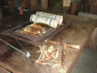 Bamboo shoots and rice boiling in bamboo sections on barbecue grill