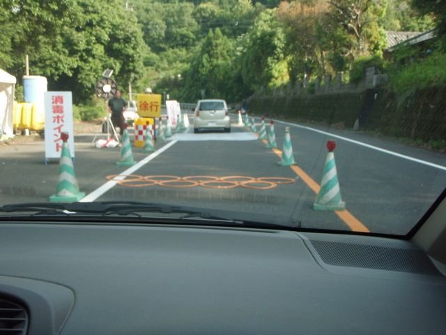 Mountain Roads have plastic Speed bumps and several workers overseeing drivers as they pass among traffic cones to pass over disinfectant mats at 10 km per hour.